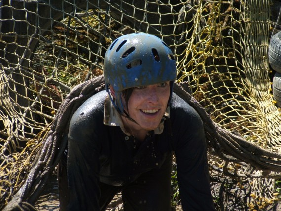 A adult going through the last obstacle on the assault course